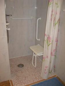 douche de plain-pied avec siège et barre de maintien dans la chambre handicapé