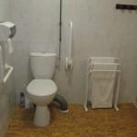 Toilettes surélevé et barre de maintien dans la chambre handicapé